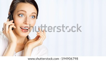 Young happy smiling business woman with cell phone, at office, with copyspace area - stock photo