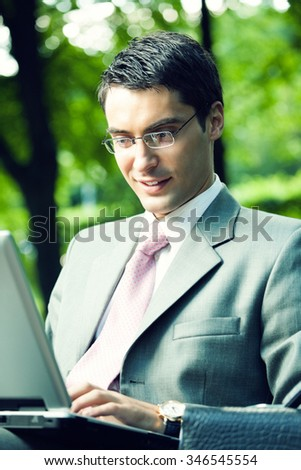 Young happy smiling businessman working with laptop, outdoors - stock photo