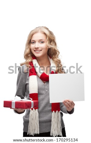young happy smiling casual  blond woman holding red christmas gift and sign isolated on white