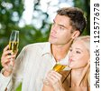 Young happy smiling cheerful attractive couple celebrating with glasses of champagne, outdoor - stock photo