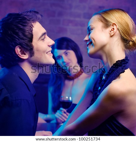 Young happy smiling couple and woman looking at them at club. Focus on couple. - stock photo