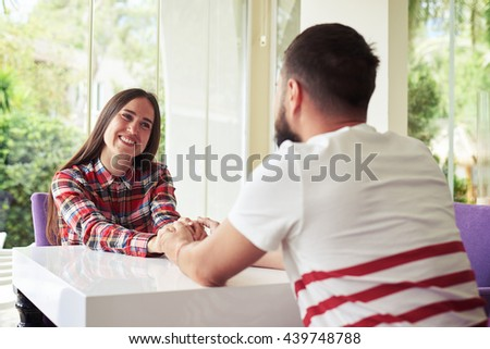 Young happy smiling couple is holding hands while having a romantic date on a bright cozy terrace with garden view