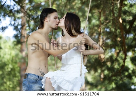Young happy smiling embracing couple swinging outdoor in nature