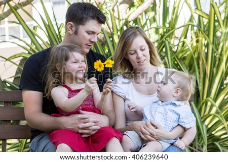 Young happy, smiling family - Parents with two young children sitting in garden - stock photo