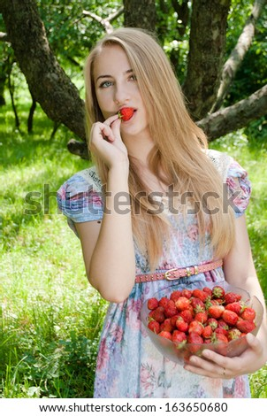 Young happy smiling & looking at camera teen girl eating strawberry from huge bowl on summer day outdoors - stock photo