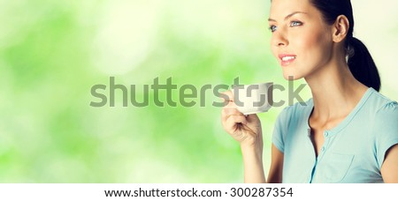 Young happy smiling lovely brunette woman drinking coffee, outdoor, with blank copyspace area for text or slogan