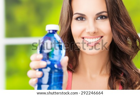 Young happy smiling lovely woman with bottle of water, outdoors - stock photo