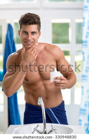 Young happy smiling man applying cream lotion on face - stock photo