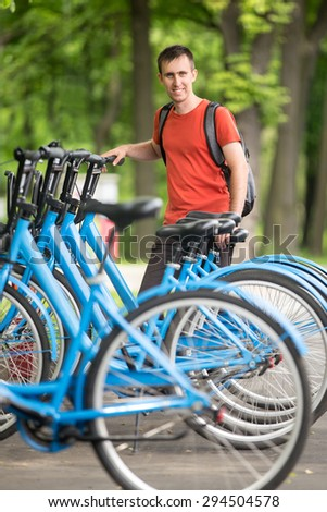 Young happy smiling man standing at rentable city bikes parking lot, choosing bicycle for ride - stock photo