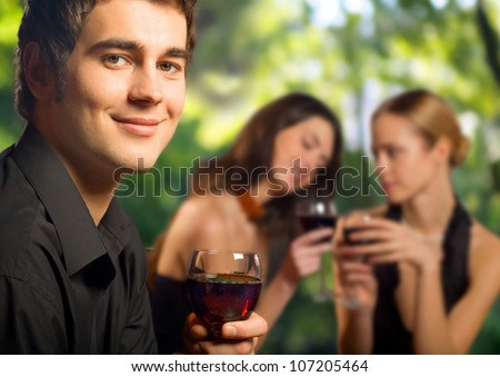 Young happy smiling man with a glass of red wine celebrating at restaurant, bar or cafe - stock photo