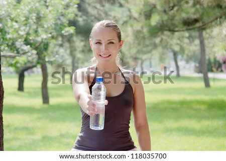 Young happy smiling sport fitness female outside on summer. Woman holding a bottle of cold water in her hand after outdoor exercise in green park - stock photo