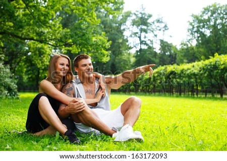 Young happy smiling sporty couple sitting on a meadow in a park