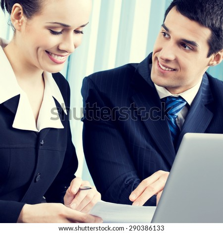 young happy smiling successful businesspeople working with document and laptop at office
