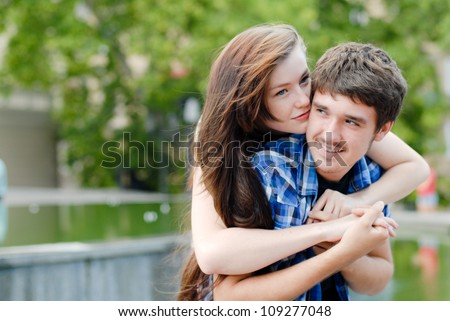 Young happy smiling teen couple embracing on green park background - stock photo