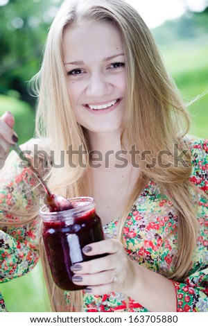 Young happy smiling teen girl eating strawberry jam & looking at camera on summer outdoors background