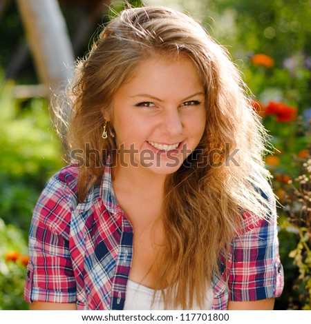 Young happy smiling teenage girl outdoors portrait on the bright day of summer background - stock photo