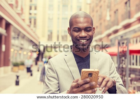 Young happy smiling urban professional man using smart phone. Businessman holding mobile smartphone using app texting sms message wearing jacket - stock photo
