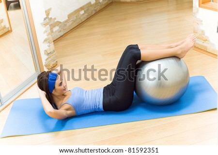 Young happy smiling woman doing fitness exercises with fit ball at home - stock photo
