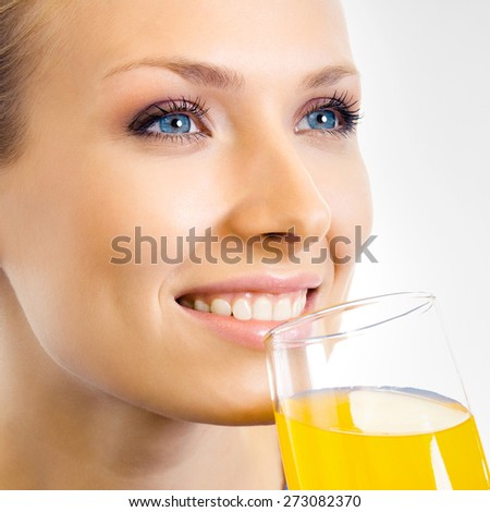 Young happy smiling woman drinking orange juice, on grey background - stock photo