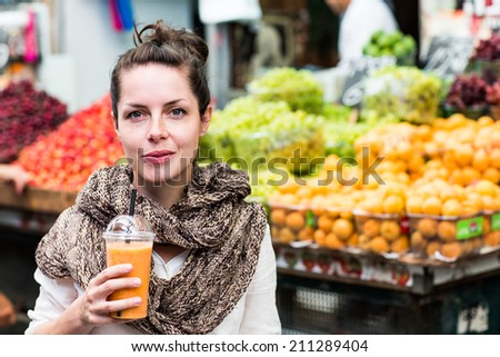 Young happy smiling woman drinking orange juice outdoor in the market with colorful background of fruit. - stock photo