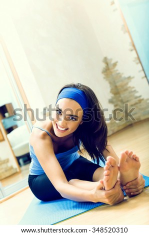 Young happy smiling woman exercising at home