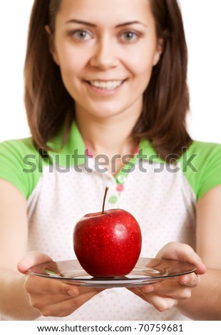 Young happy smiling woman give red apple on plate. Focus on apple