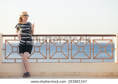 Young happy smiling woman in cute straw hat and casual summer dress standing on sunny street of sea town, holding cellphone, looking at screen, using app, messaging
