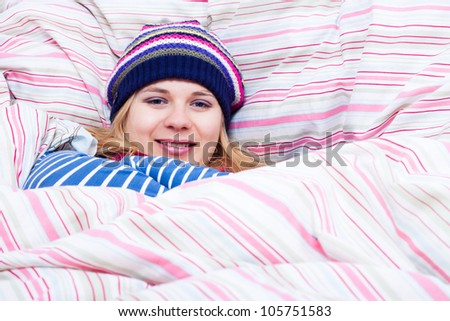 Young happy smiling woman in winter hat wrapped in duvet.