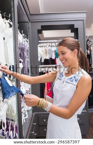 Young happy smiling woman looking at clothes in the clothes store