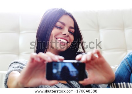 Young happy smiling woman making self photo with her smartphone - stock photo