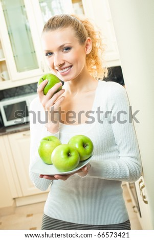 Young happy smiling woman with apples, at home - stock photo