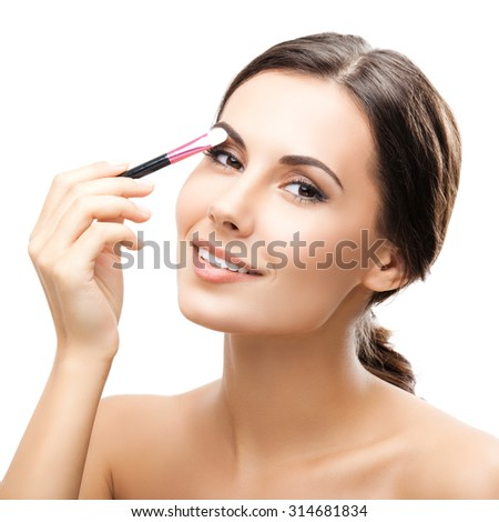 Young happy smiling woman with cosmetics brush, isolated over white background - stock photo