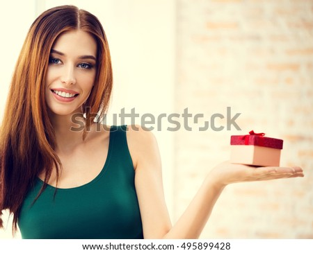 Young happy smiling woman with gifts, at home, indoors. Celebration and holiday sale concept with caucasian beautiful model. Blank copyspace area for advertising, slogan or text message.