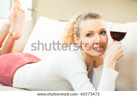 Young happy smiling woman with glass of red wine, at home - stock photo
