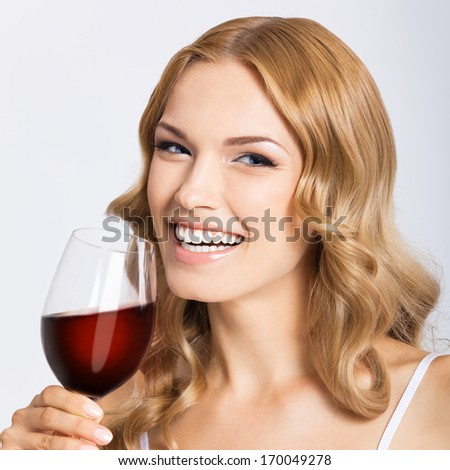 Young happy smiling woman with glass of red wine, over gray background