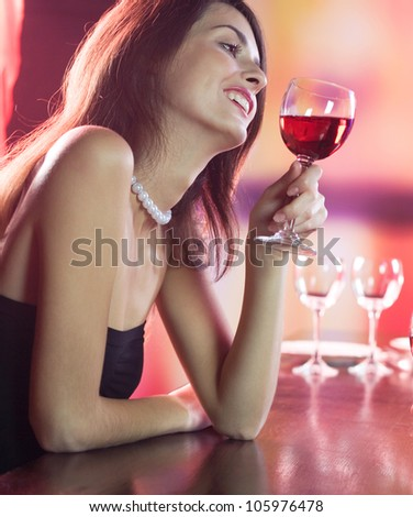 Young happy smiling woman with glass of redwine at restaurant or club