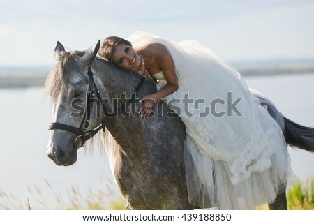 Young happy smiling woman with horse. bride on the horse - stock photo