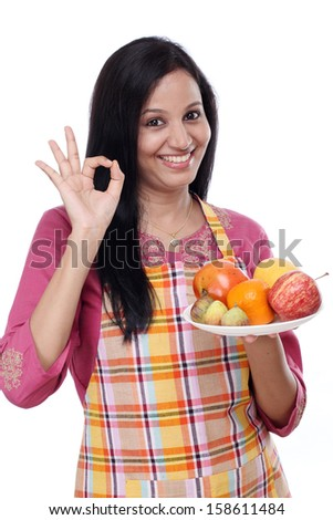 Young happy smiling woman with plate of fruits - stock photo