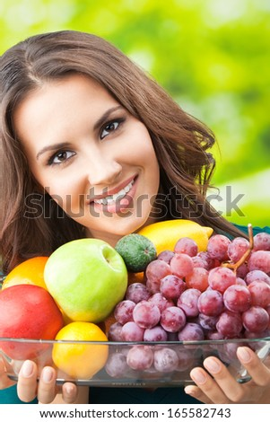 Young happy smiling woman with plate of fruits, outdoors
