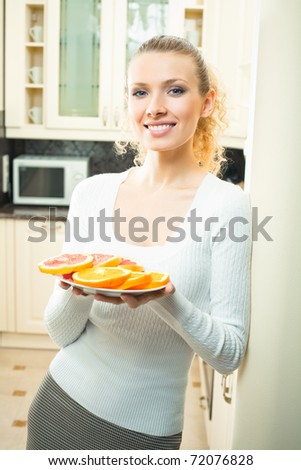 Young happy smiling woman with plate of oranges and grapefruit at home