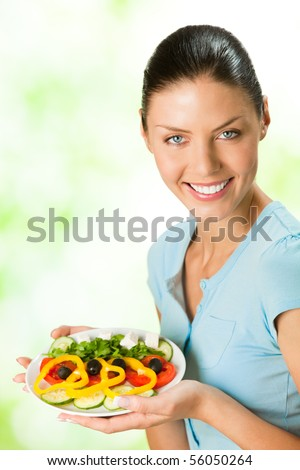 Young happy smiling woman with salad, outdoor - stock photo