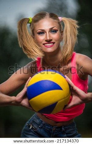 Young happy sport woman giving you a volleyball ball  - stock photo