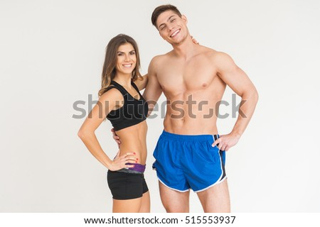 Young happy sportsmen couple woman and man in gym looking to the camera