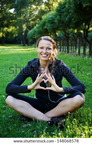 Young happy sporty girl showing heart sign with her hands on a meadow in a park - stock photo
