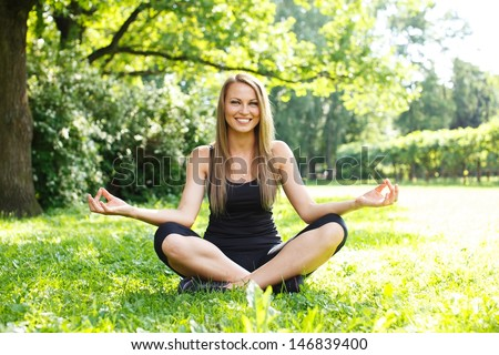 Young happy sporty girl sitting in yoga pose on a meadow in a park - stock photo