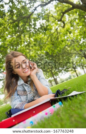 Young happy student lying on the grass on the phone on college campus - stock photo