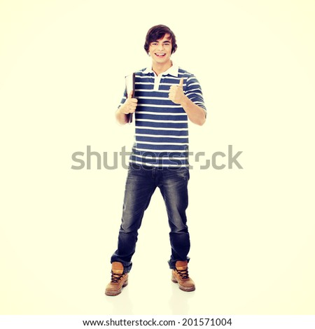 Young happy student man with notebook gesturing OK - stock photo