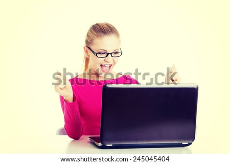 Young happy student woman sitting in front of laptop.