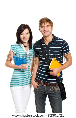Young happy students couple smiling, holding notebooks, looking at camera, isolated over white background - stock photo