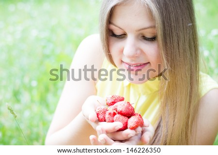 Young happy teen girl eating strawberry from huge bowl on summer day outdoors - stock photo